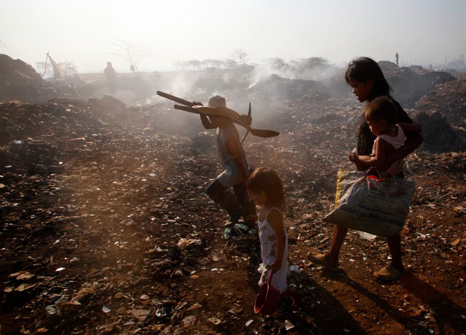People walk on Smokey Mountain, a small hill made entirely of burnt garbage, in a slum area near