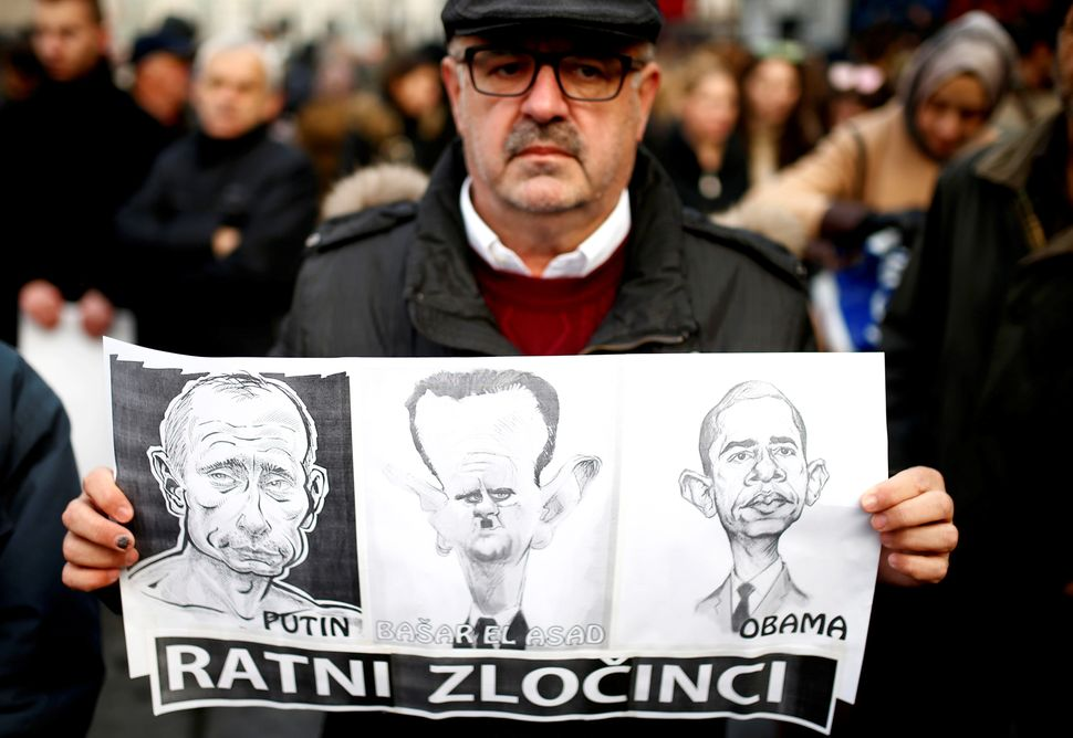 A man holds a placard with caricatures of Russian President Vladimir Putin, Syrian President Bashar Assad and U.S. President