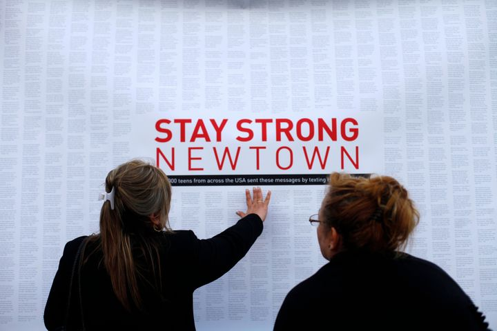 A woman touches a printout of messages from teenagers around the United States at a memorial for the victims of the Sandy Hoo