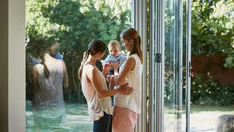 Happy lesbian couple with baby boy standing by glass window