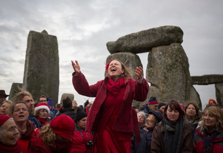 A woman leads the Shakti Sings choir as Druids, Pagans and revelers gather in the center of Stonehenge for a winter sols