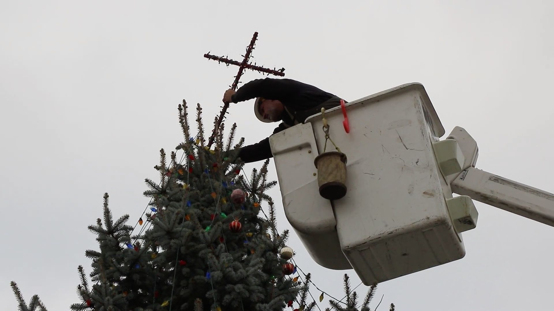 A worker removes a crucifix from the top of a Christmas tree located in an Indiana town square