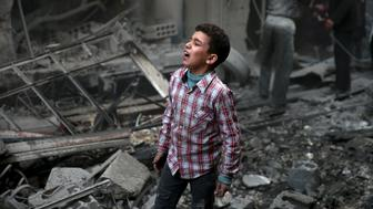 A boy reacts in a site hit by what activists said were airstrikes carried out by the Russian air force in the town of Douma, eastern Ghouta in Damascus, Syria January 10, 2016. REUTERS/Bassam Khabieh