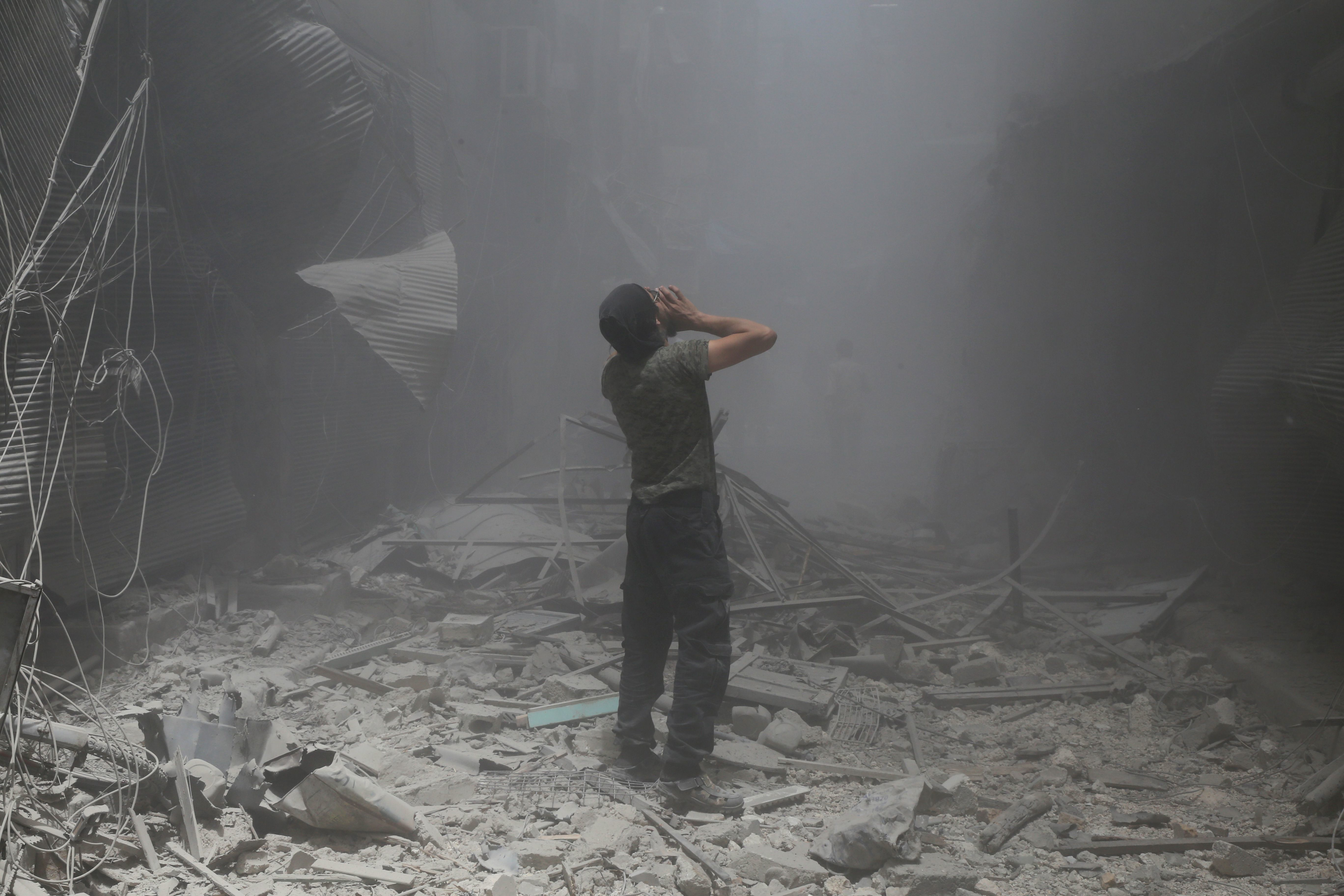 TOPSHOT - A Syrian man reacts following a reported air strike by Syrian government forces in the rebel-held neighbourhood of Bustan al-Qasr on June 5, 2016. / AFP / Baraa Al-Halabi        (Photo credit should read BARAA AL-HALABI/AFP/Getty Images)