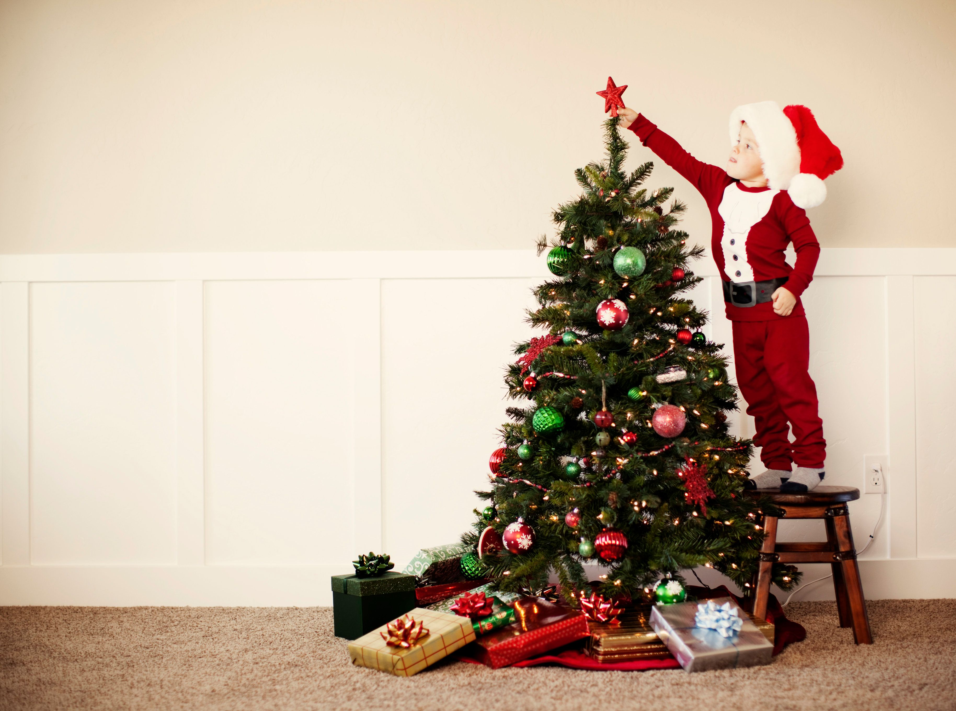 A young boy dressed in Santa pajamas places a star a top the Christmas tree.