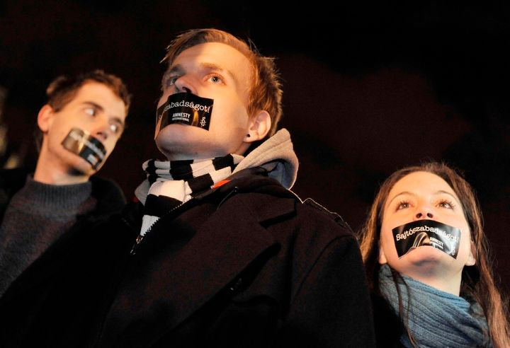 Hungarian Amnesty International activists protest with taped mouth during a demonstration against the government's new