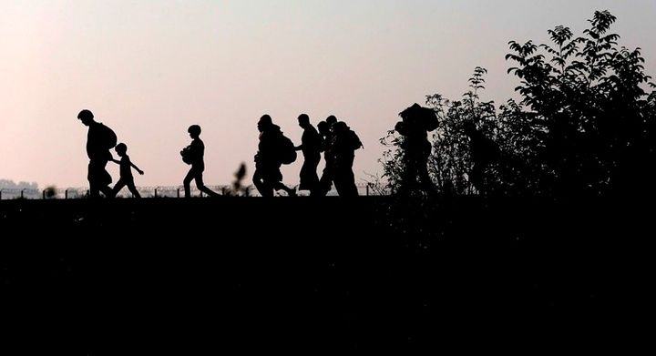 Migrants walk along the railway track after crossing the border between Serbia and Hungary on Sept. 13, 2015.