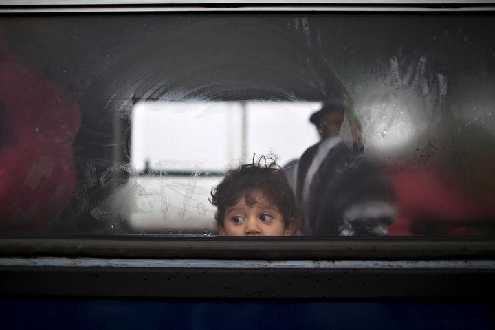 A Syrian refugee child looks out of a bus that will take him and his family to the center for asylum seekers in southern Hung