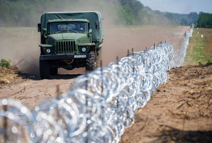 A Hungarian military truck passes a barbed-wire section of a 108-mile (175km) fence on Hungary's southern border with S