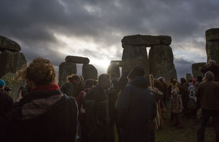 The sun peeks through clouds during a winter solstice ceremony at the ancient neolithic monument of Stonehenge near