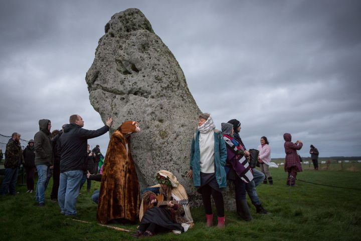 People gather around a stone during the winter solstice ceremony at Stonehenge on December 22, 2015.