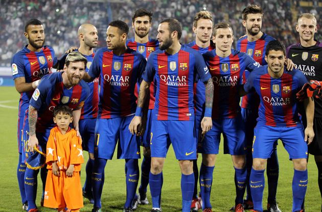 Lionel Messi (second from left) and the FC Barcelona team pose for photos with Murtaza Ahmadi before...