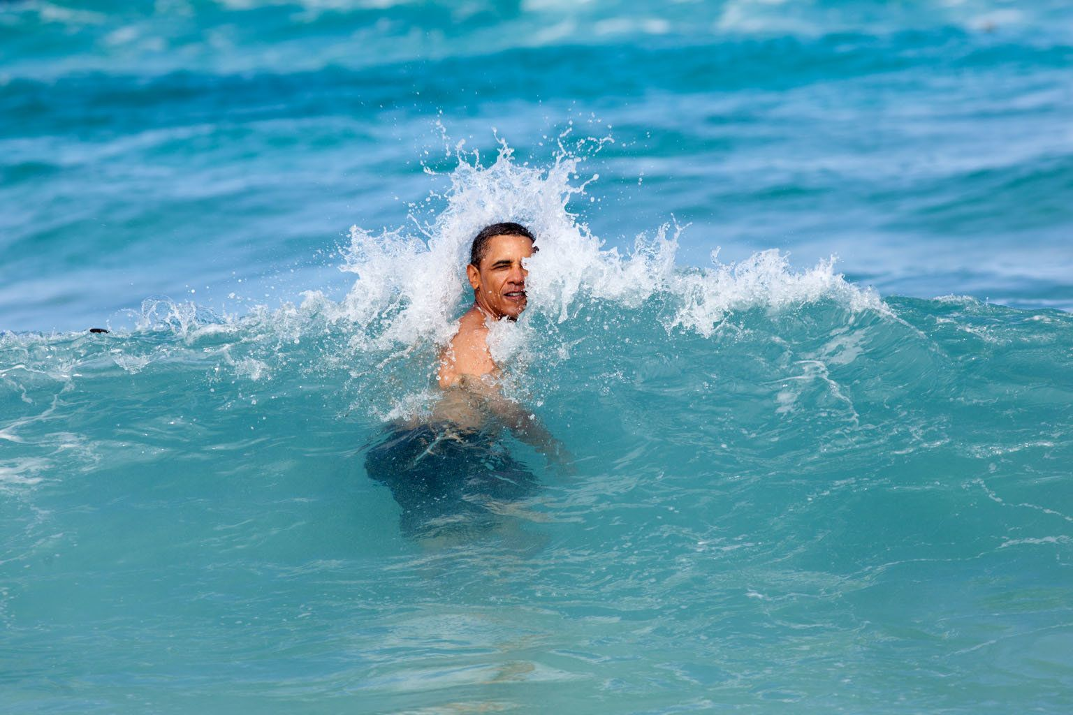 KANEOHE BAY, HI - JANUARY 1:  In this handout from the White House, U.S. President Barack Obama jumps into the ocean at Pyramid Rock Beach January 1, 2013 in Kaneohe Bay, Hawaii. Obama is currently on vacation in his native state.  (Photo by Pete Souza/The White House via Getty Images)