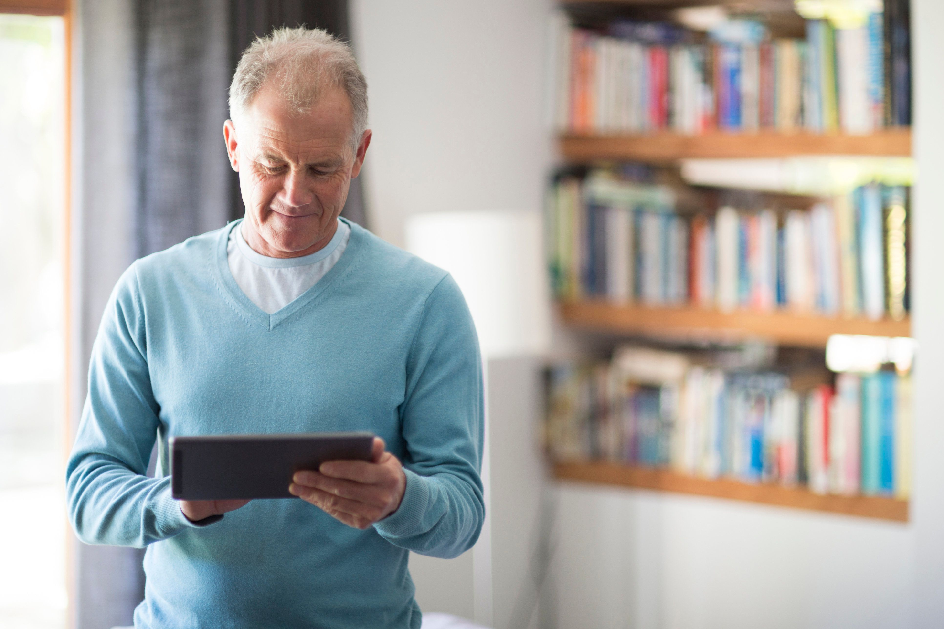 Senior man, aged 61,  using a tablet computer at home