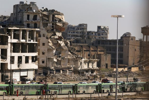 Buses are seen parked in Aleppo's government controlled area of Ramouseh, as they wait to takecivilians...