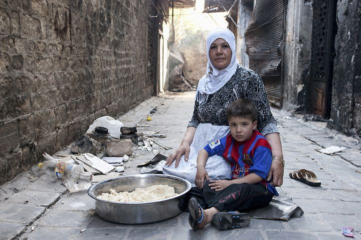 Jdaideh, Aleppo. A displaced mother tends to her child and bakes bread.