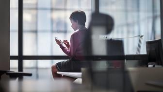 Woman sitting on desk touching smart phone