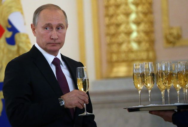 Putin takes a glass of champagne during the reception for new foreign ambassadors at the Grand Kremlin...