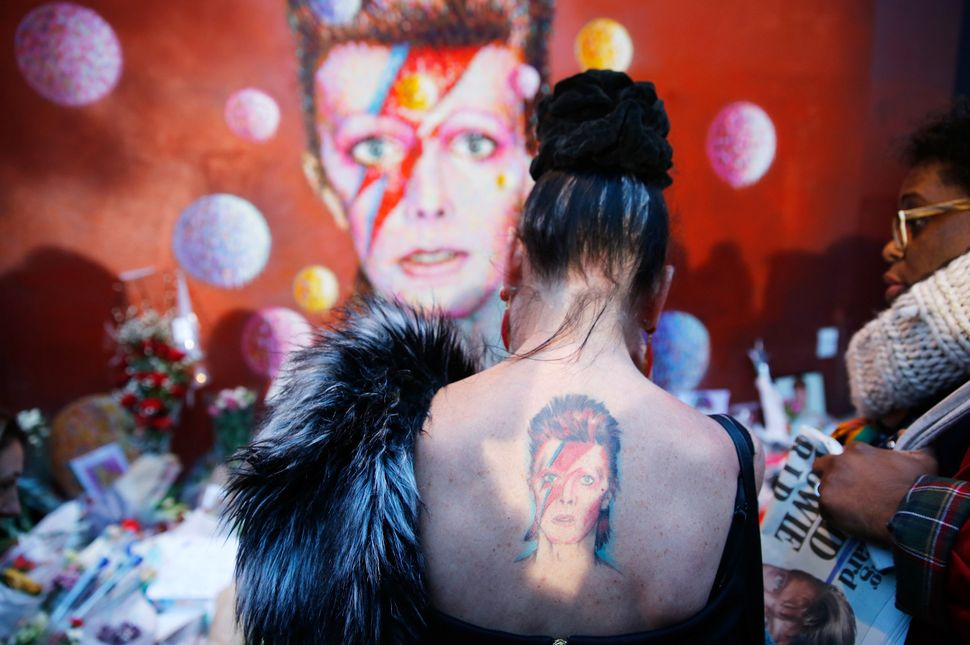 A woman with a Ziggy Stardust tattoo visits a mural of David Bowie in Brixton, south London, on Jan.11. Bowie, a music