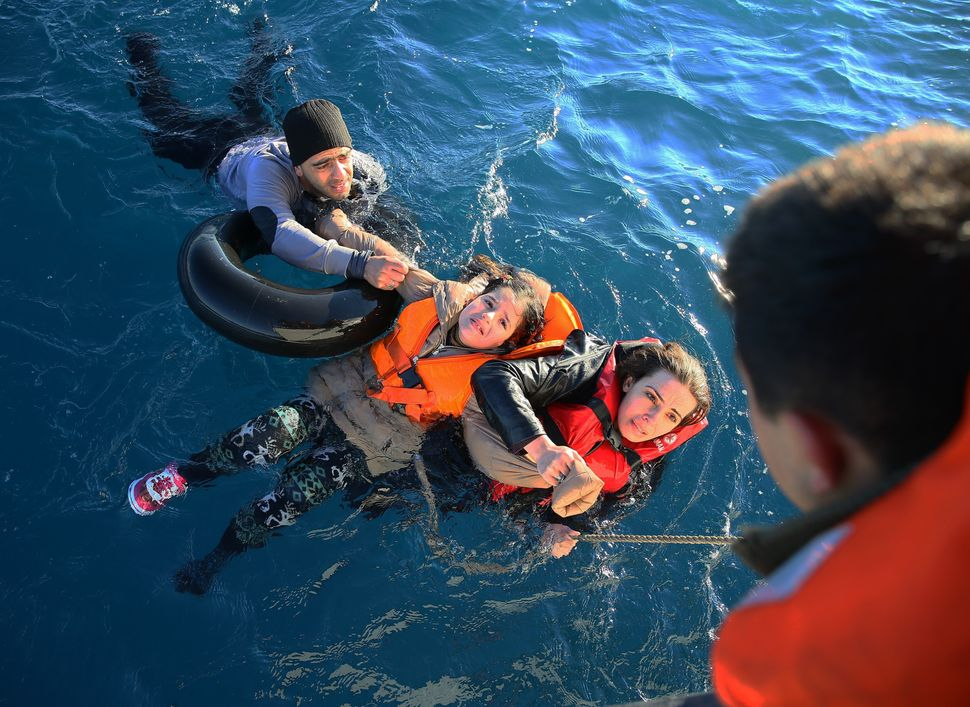 Turkish Coast Guard personnel help refugees as they swim with buoys, after they toppled over a fisherman dinghy en route to G