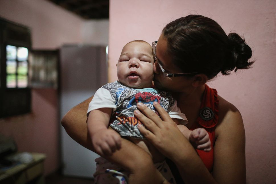 David Henrique Ferreira, 5 months, who was born with microcephaly, is kissed by his mother, Mylene Helena Ferreira, on Jan. 2