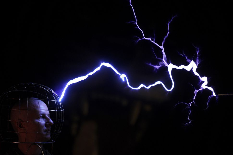 This photo taken on Feb. 13, shows Oleg Melnik, wearing a wire helmet, getting electrical discharges of Tesla coil inside a F