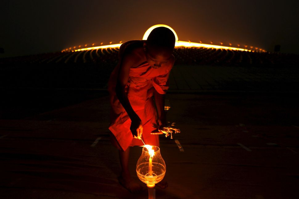 A Buddhist monk lights a candle at Wat Phra Dhammakaya during a ceremony on Makha Bucha Day in Pathum Thani province, north o