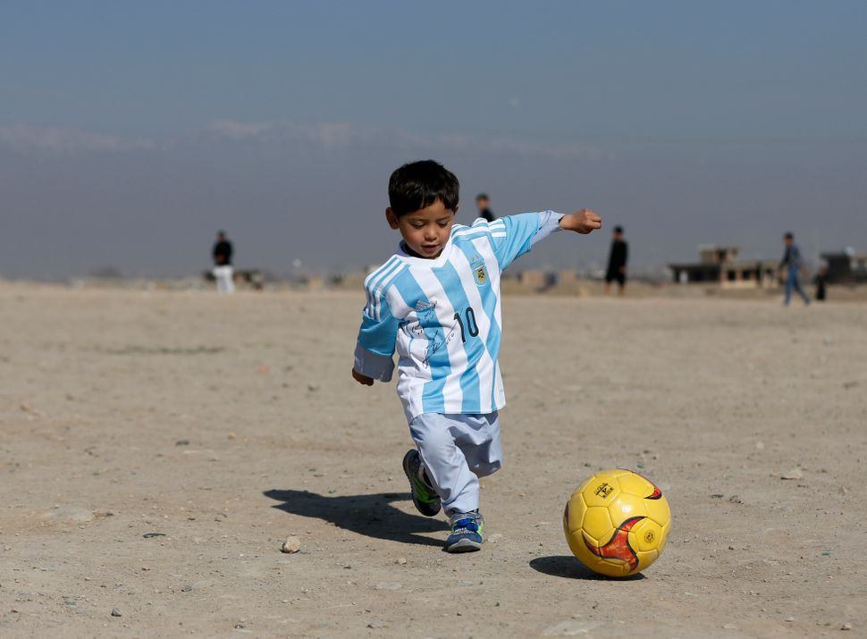 Five-year-old Murtaza Ahmadi, an Afghan Lionel Messi fan, wears a shirt signed by Barcelona star Lionel Messi as he plays foo