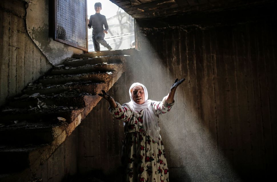 A woman reacts while walking among the ruins of damaged buildings following heavy fighting between government troops and Kurd