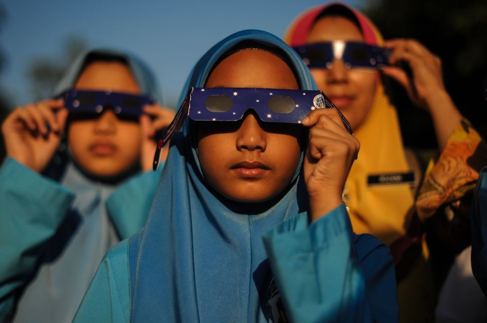 Malaysian schoolchildren wearing glasses with special filters watch the partial solar eclipse at the National Planetarium in