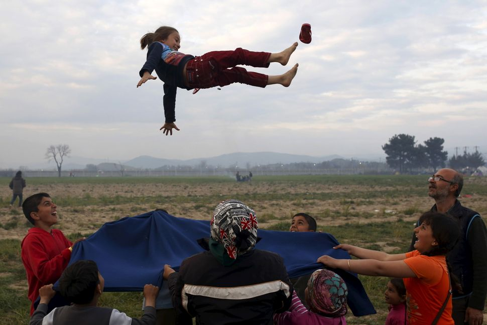 Children play at a makeshift camp for migrants and refugees bythe Greek-Macedonian border near the village of Idomeni,