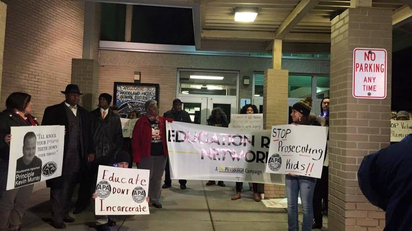 Image of a group of protestors outside of a school building holding signs  to show solidarity