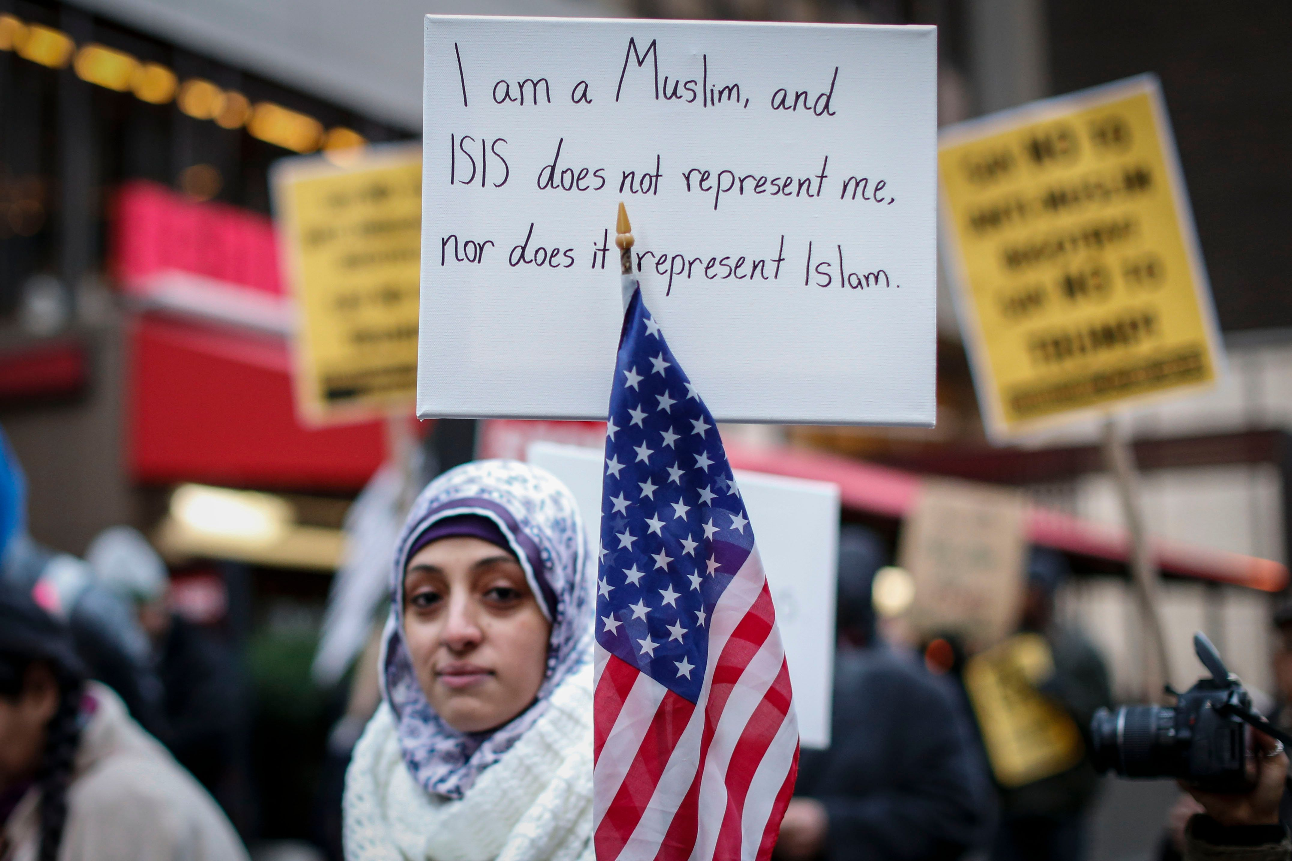 A Muslim woman holds a poster during a protest  against Donald Trump on December 20, 2015 in New York. Republican presidential hopeful Donald Trump proposed a call for a ban on Muslims entering the United States. AFP PHOTO/KENA BETANCUR / AFP / KENA BETANCUR        (Photo credit should read KENA BETANCUR/AFP/Getty Images)
