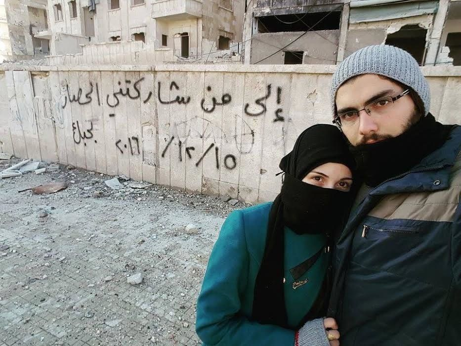 Marwa and Salih pose in front of a graffiti message they left in