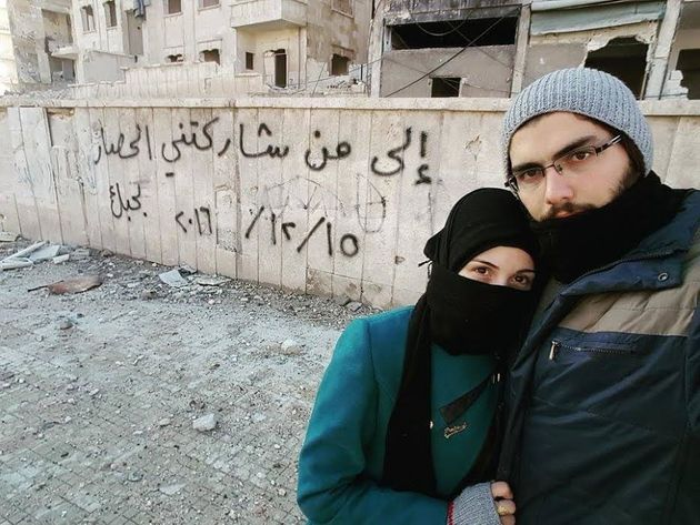 Marwa and Salih pose in front of a graffitimessage they left in