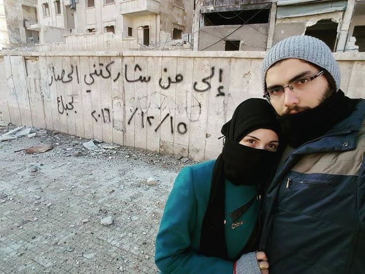 Marwa and Salih pose in front of a graffiti message they left in Aleppo.