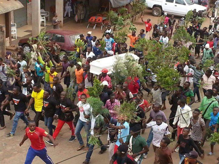 Demonstrators in Buea walk a coffin of a murdered civilian.