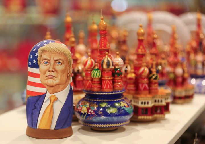 A martyoshka doll showing Donald Trump, U.S. president elect, sits beside painted wooden models of St. Basil's cathedral in a