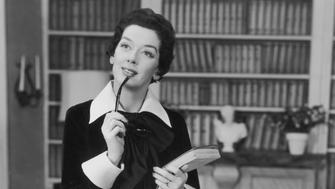 Actress Rosalind Russell (1907-1976) pictured seated on the edge of a desk while putting the arm of a pair of glasses to her lips with one hand and holding a stack of papers in the other in a scene from the film 'Auntie Mame', USA, circa 1958. Russell played 'Mame Dennis' in the film. (Photo by Pictorial Parade/Archive Photos/Getty Images)