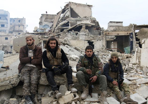 Rebel fighters sit on the rubble of damaged buildings as they wait to be evacuated from a rebel-held...