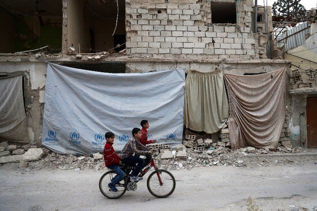 Syrian children ride a bicycle in the rebel-held town of Douma on the eastern outskirts of the capital Damascus on November 13 2016 Douma the largest town in the Eastern Ghouta area with more than 100000 residents is surrounded and regularly shelled by regime forces