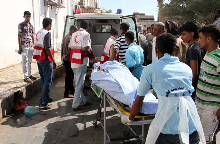 Yemeni medics transport a body into a hospital in Aden on December 18, 2016, after a suicide bomber targeted a crowd of soldi