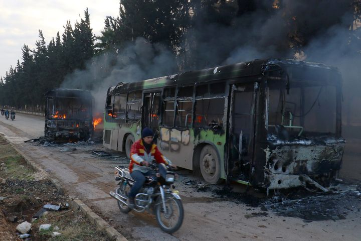A man on a motorcycle drives past burning buses while en route to evacuate ill and injured people in Idlib province, Syria De
