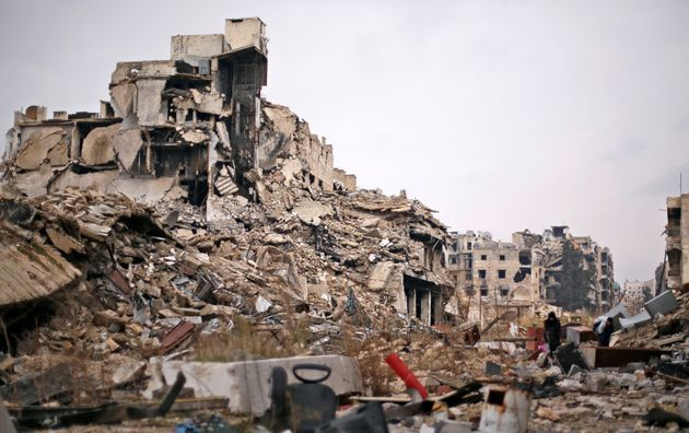 People carry belongings as they walk on the rubble of damaged buildings in the government controlled...