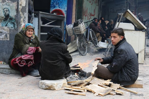 People warm themselves around a fire while waiting to be evacuated from a rebel-held sector of eastern...