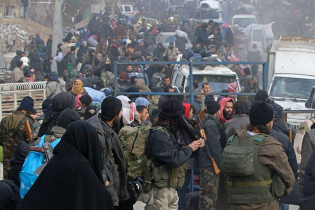 Rebel fighters and civilians gather as they wait to be evacuated from a rebel-held sector of eastern...