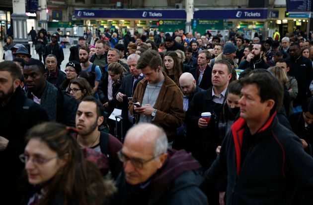 Passengers queue for a reduced during the Southern railway strike at Victoria station in