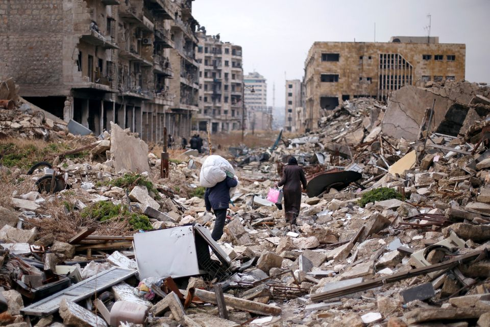 People walk amid the rubble as they carry belongings that they collected from their houses in the government controlled area