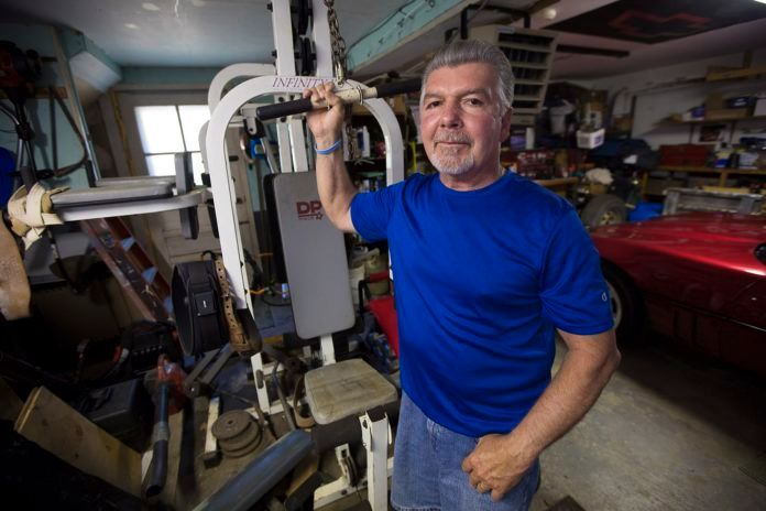 <em>Mike Dennen, who was diagnosed with mesothelioma four years ago, in his garage in Bourne where he works out to keep fit.