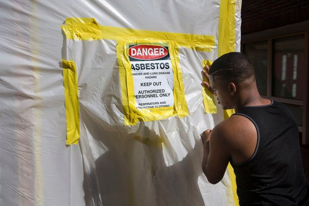 <em>Using plastic and duct tape, a worker fabricates an asbestos containment barrier on a doorway of the Teaticket School in